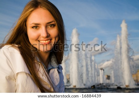 Young woman smiling at sunset in city near fountain - stock photo