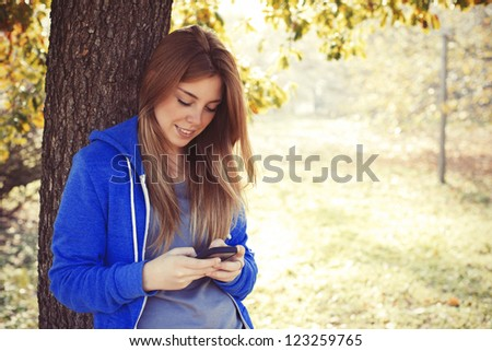 Young woman smiling at the park - stock photo