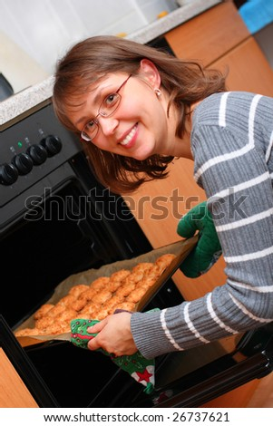 Young woman smiling, baking cookies in the kitchen - stock photo