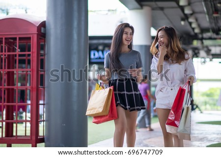 young woman smiling enjoy shopping discount sale and many bags on hands at shopping mall