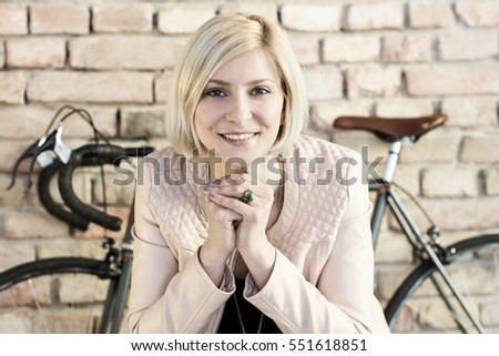 Young woman smiling front of bicycle.