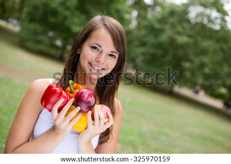 young woman smiling holding a selection of fruit and vegetables - stock photo