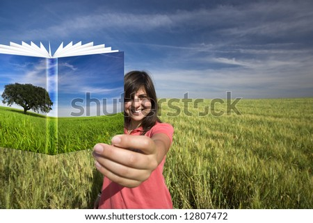 young woman smiling holding book with colorful cover - stock photo