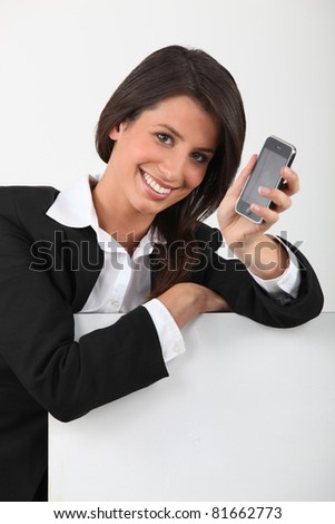 Young woman smiling  holding mobile telephone - stock photo