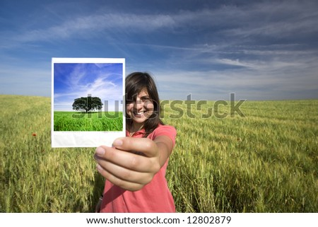 young woman smiling holding single instant photo film strip - stock photo