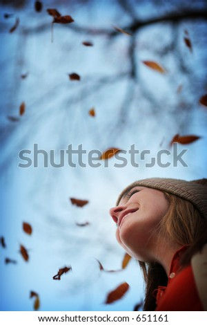 Young woman smiling in the fall leaves - stock photo