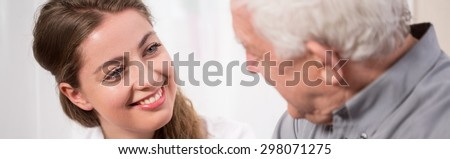 Young woman smiling to elder man - stock photo