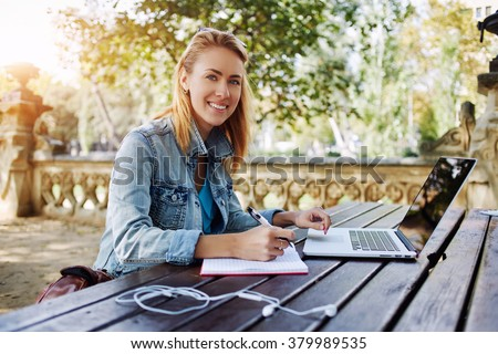 Young woman smiling to the camera while sitting with notepad and laptop computer in beautiful city park, happy Caucasian female posing during work on portable net-book outdoors in warm spring day