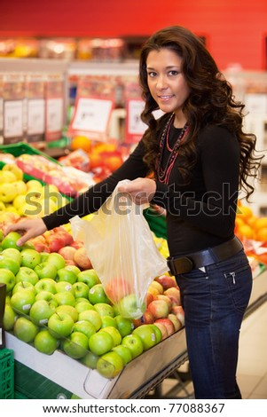 Young woman smiling while buying fruits in the supermarket - stock photo