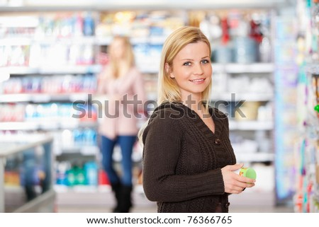 Young woman smiling while holding goods in the supermarket with people in the background - stock photo