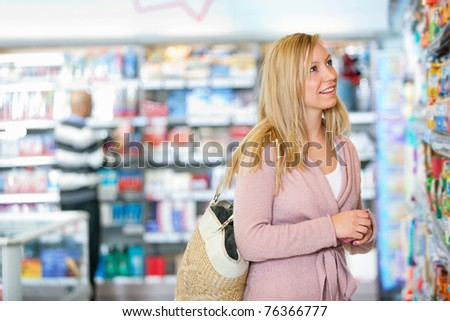 Young woman smiling while looking at goods in the supermarket with people in the background - stock photo