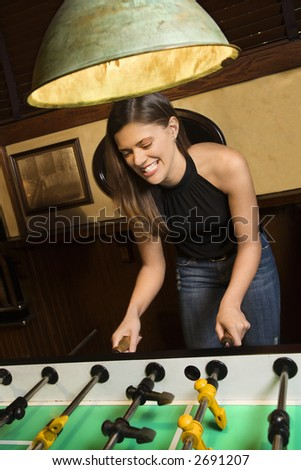 Young woman smiling while playing foosball game at pub. - stock photo