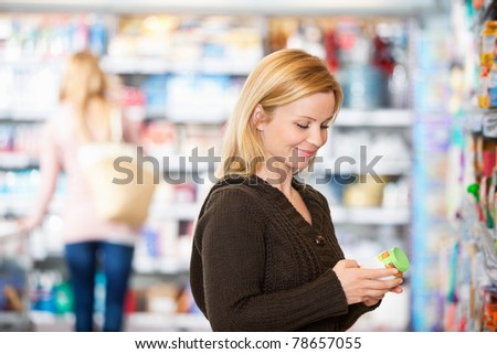 Young woman smiling while shopping in the supermarket with people in the background - stock photo