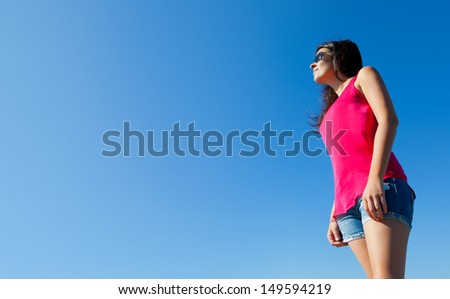 Young Woman Smiling with a Blue Sky Background - stock photo