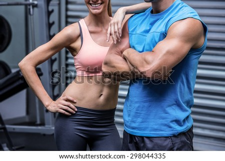 Young woman smiling with a young man in the crossfit gym - stock photo
