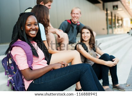 Young woman smiling with friends in the background on stairs - stock photo