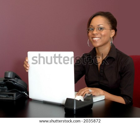 Young woman smiling with laptop computer in office setting - stock photo