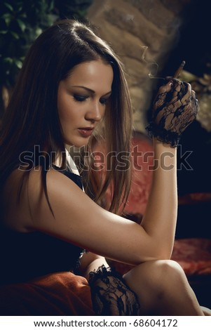 Young woman smoking cigarette in vintage interior - stock photo