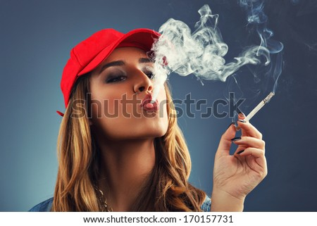 Young woman smoking cigarette on a blue background - stock photo