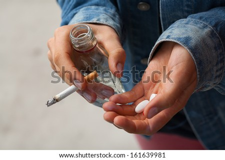 Young woman smoking cigarettes, drinking vodka and taking pills