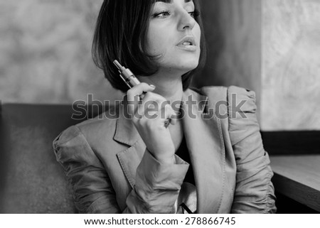 young woman smoking electronic cigarette - stock photo