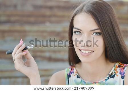 Young woman smoking electronic cigarette (e-cigarette) - stock photo