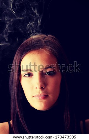 Young woman smoking over black background  - stock photo