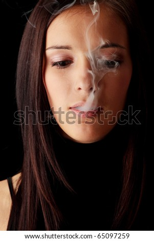 Young woman smoking over black background