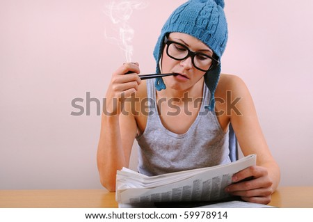 Young woman smoking pipe and reading a newspaper - stock photo