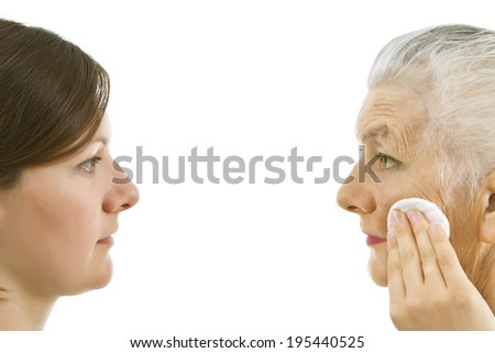 young woman smoothing out an old woman's wrinkles   with a make up pad - stock photo