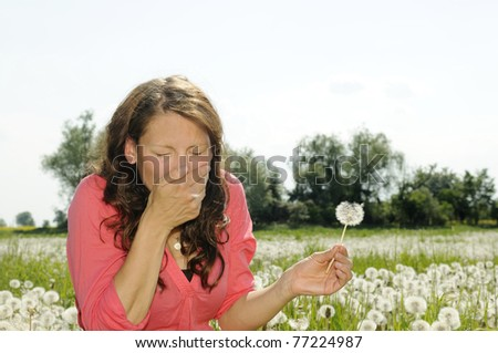 young woman sneezes on a flower meadow - stock photo