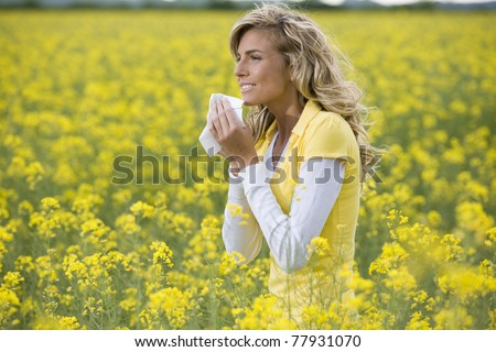 Young woman sneezing in a flowers meadow. Concept: seasonal allergy. - stock photo