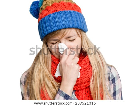Young woman sneezing in a tissue in winter bright hat isolated on white background - stock photo