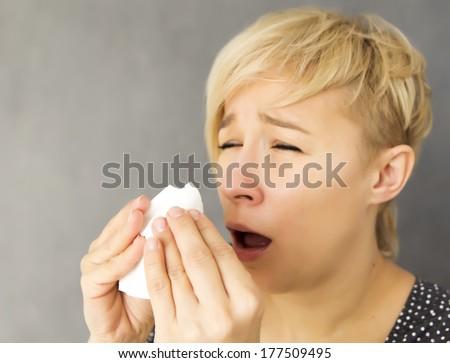 young woman sneezing into handkerchief - stock photo