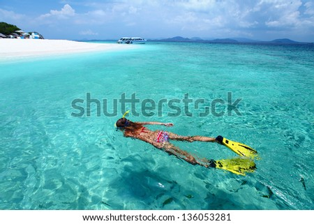 Young woman snorkeling in a clear shallow sea near a beach with white sand - stock photo