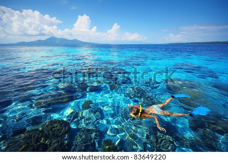 Young woman snorkeling in transparent shallow blue sea above coral reef.