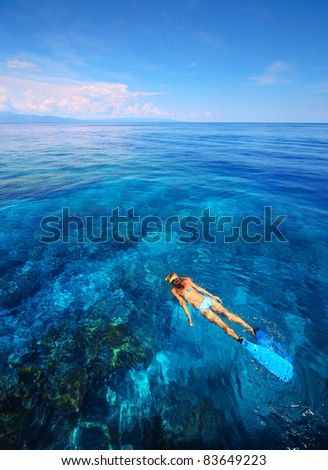 Young woman snorkeling in transparent shallow blue sea above coral reef. - stock photo