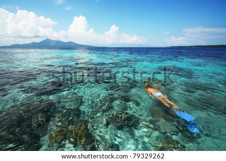Young woman snorkeling in transparent shallow sea above coral reef. - stock photo