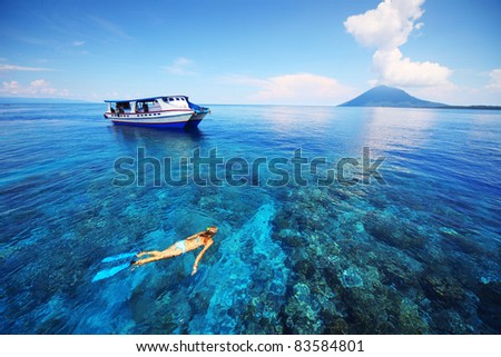 Young woman snorkeling in transparent shallow sea near boat