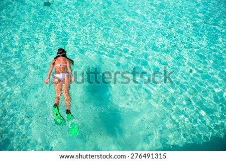 Young woman snorkeling in tropical water on vacation - stock photo