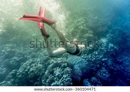 young woman snorkling under water - stock photo