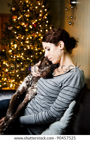 Young woman snuggling with her dog at Christmas time - stock photo