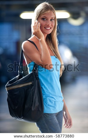 Young woman speaking on the phone while at an underground car park - stock photo