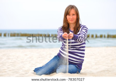young woman spilling sand on the beach