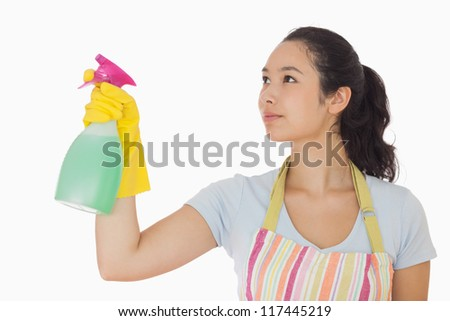 Young woman spraying cleaner in rubber gloves and apron - stock photo