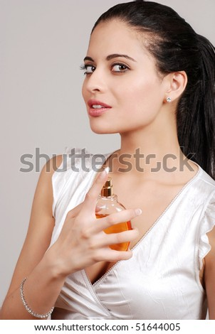 young woman spraying perfume - stock photo
