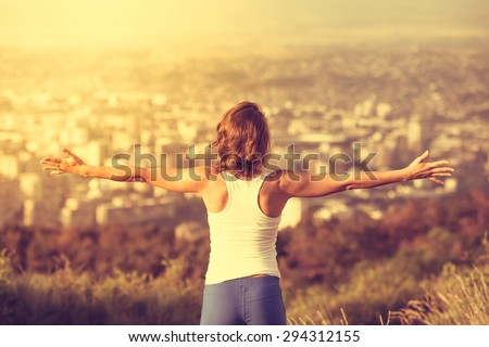 Young woman spreading hands wide open with city on background. Freedom concept. Love and emotions, woman happiness. Toned image - stock photo