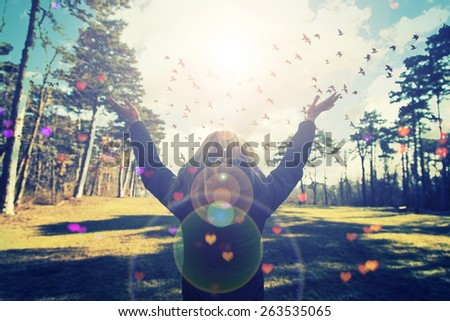 Young woman spreading hands with joy and inspiration facing the sun,freedom concept,bird flying above sign of freedom and liberty,happiness  - stock photo