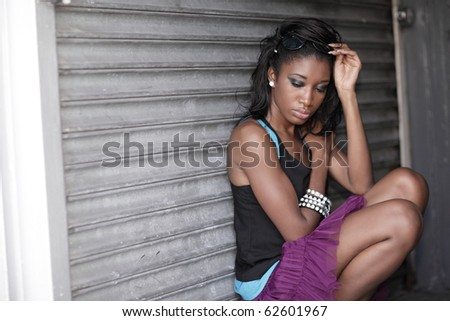 Young woman squatting in an urban setting - stock photo