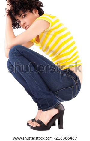 Young woman squatting with curly hair and shirt with yellow stripes. - stock photo